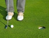 短いボールを置くゴルフ緑の穴コース男 — ストック写真