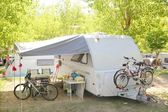 Camping camper caravan trees park bicycles — Stock Photo
