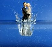 Wedding figurine falling down to blue water — Stock Photo