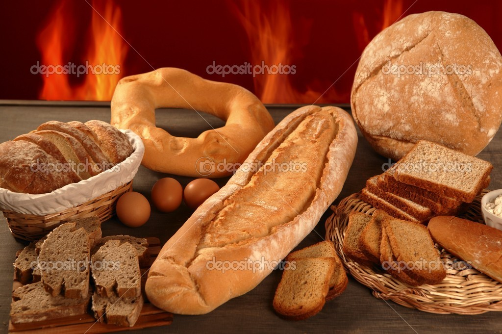 Bread still life with varied shapes and bakery fire in background — Stock Photo #5500728