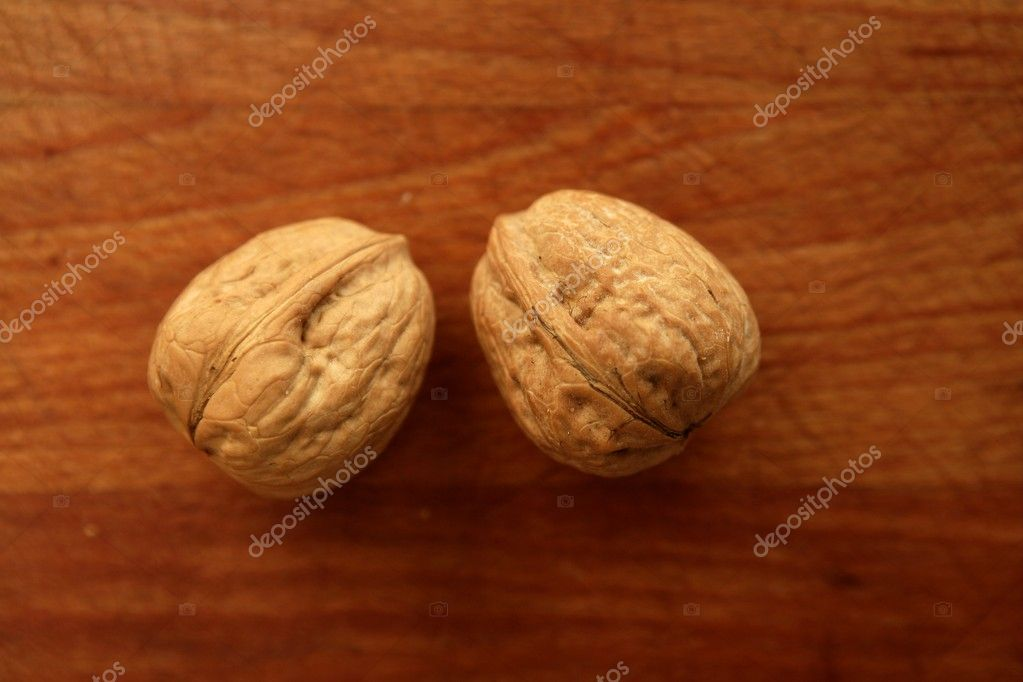 Two walnuts on a golden wood aged table — Stock Photo #5502045