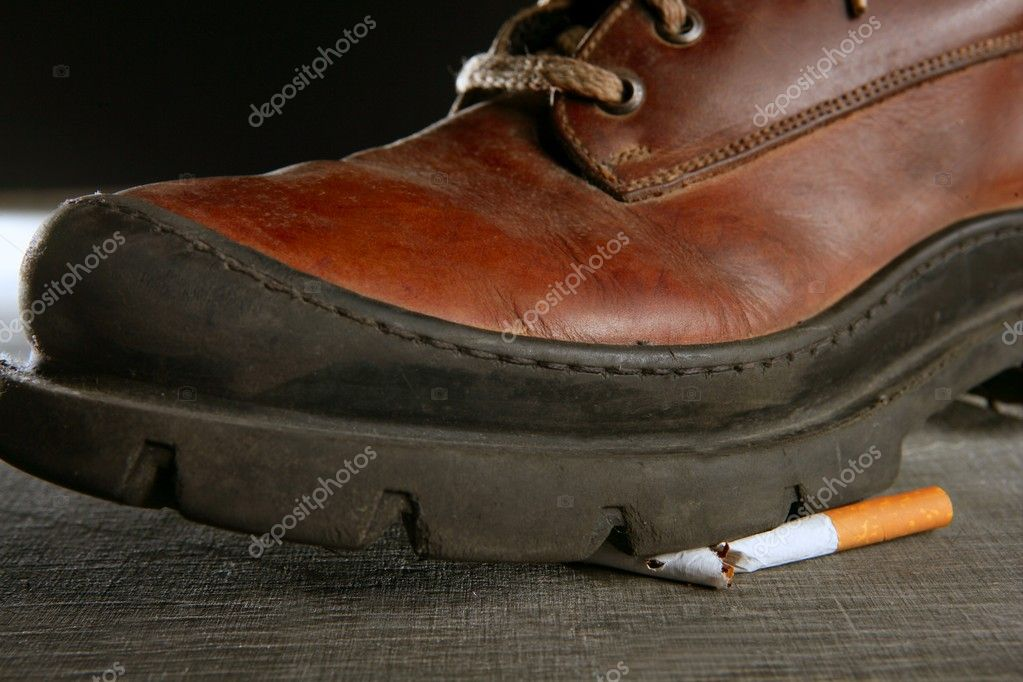 Broken cigarette tread by a boot, tobacco addiction metaphor — Stock Photo #5503269