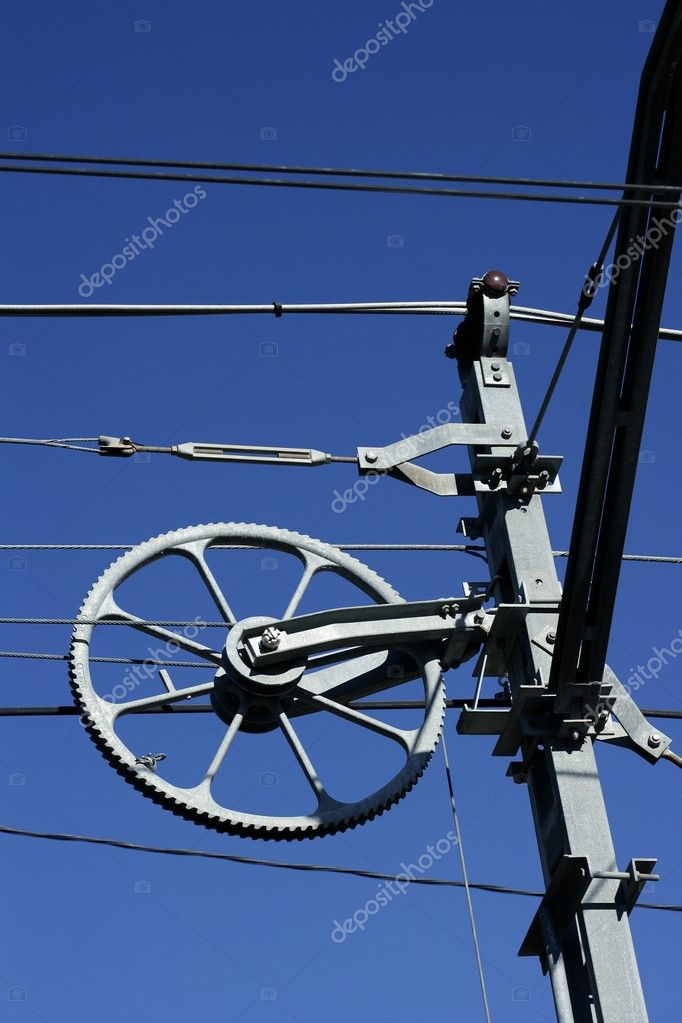 Electric railway steel wires infrastructure over vivid blue sky, wheel.  Stock Photo #5504991