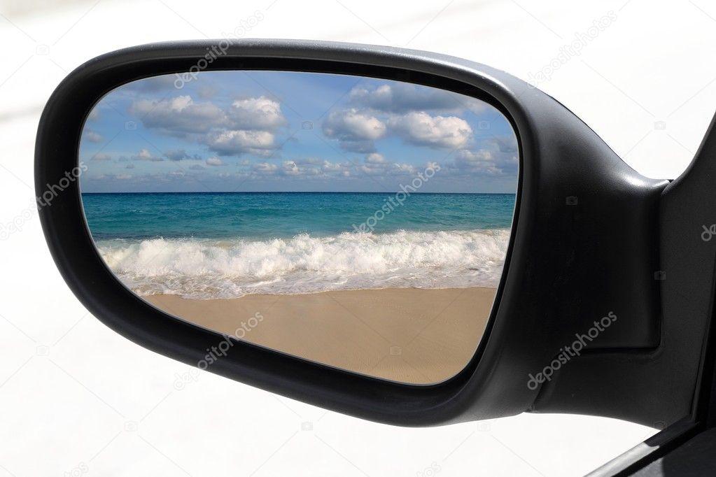Rearview car driving mirror tropical caribbean beach - stock image