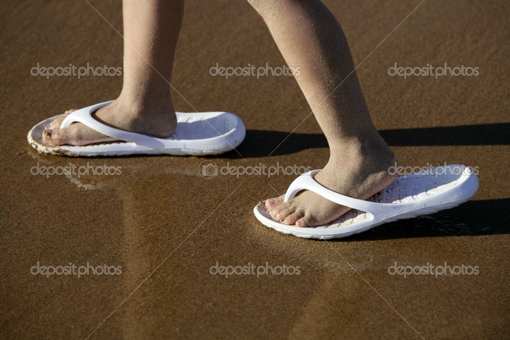 Adult shoes for children feet on beach sand outdoor — Stock Photo #5507740