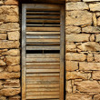 Aged wood door on masonry stone wall - Stock Photo