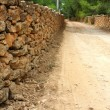 Masonry stone wall fence around sand soil track - Photo