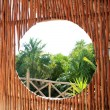 Circle window in wooden sticks cabin tropical Jungle — Stock Photo
