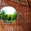 Circle window in wooden sticks cabin tropical Jungle — Stock Photo #5511433