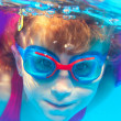 Underwater swimming girl goggles blue water — Stock Photo