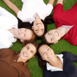 图库照片: Friends happy group in circle together on grass