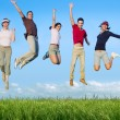 Jumping young happy group in meadow — Stock Photo #5511665