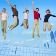 Jumping young group on city buildings — Stock Photo
