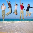Jumping young happy group tropical beach — Stock Photo