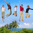 Jumping young happy group tropical beach — Stock Photo #5511677