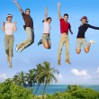 Jumping young happy group tropical beach - Stock Photo