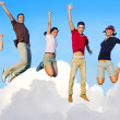 Jumping young happy group flying in sky — Stock Photo
