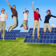 Jumping young happy group green solar energy — Stock Photo #5511679