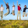 Jumping young happy group on yellow flowers — Stock Photo