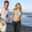 Couple running at beach, young and beautiful — Stock Photo