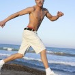 Young man jumping at the beach — Stock Photo