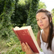 Beautiful woman reading a book in forest, nature - Stockfoto