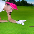 Golf green hole woman humor flicking hand a ball — Stock Photo #5512494