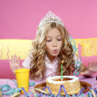 Foto Stock: Happy little blond girl blowing cake candle in a birthday party