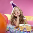 Bored little blond girl birthday party with candle cake — Stock Photo