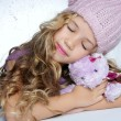 Winter fashion cap little girl hug teddy bear smiling - Stockfoto