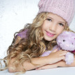 Winter fashion cap little girl hug teddy bear smiling — Stock Photo #5512659