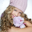 Winter fashion cap little girl hug teddy bear smiling — Stock Photo