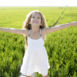 Open arms little happy girl green meadow field — Stock Photo #5512696