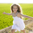 Running open arms little happy girl in meadow track — Stock Photo #5512705