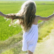 Rear view running open arms little girl in meadow track — Stock Photo #5512709