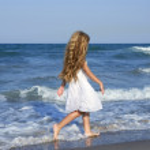 Little girl running beach in blue sea — Stock Photo