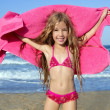 Beach little girl playing pink towel and wind — Stock Photo