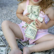 Toddler girl with lots of dollar notes — Stock Photo