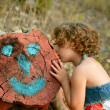Girl kiss a cutted trunk with happy face draw — Stock Photo #5512781