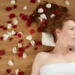 Redhead beautiful woman, rose petals on hair — Stock Photo