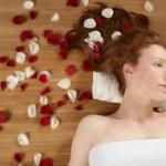 Redhead beautiful woman, rose petals on hair — Stock Photo