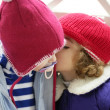 Children, winter red hat whispering in ear - Stock fotografie