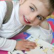 Beautiful preschooler girl studying book — Stock Photo #5513058