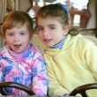 Two little sister girls driving car on fairground - Stock Photo
