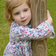 Beautiful little toddler girl hug a trunk — Stock Photo #5513171