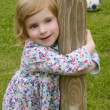 Beautiful little toddler girl hug a trunk — Stock Photo #5513175