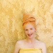 Beautiful woman with orange towel in head — Stockfoto