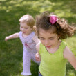 Beautifull little sisters running on the park — Stock Photo