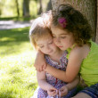 Stock Photo: Two little sister girls hug playing under tree