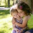 Two little sister girls hug playing under tree — Stock Photo
